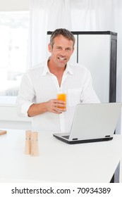 Man looking at his laptop while he is drinking orange juice