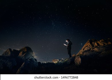 Man is looking at his phone with his head light at starry night the mountains