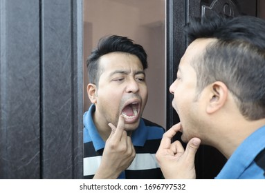 a man looking at his reflection in mirror with open mouth and checking his teeth for cavity infection and toothache