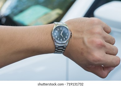 man looking at his watch on his hand