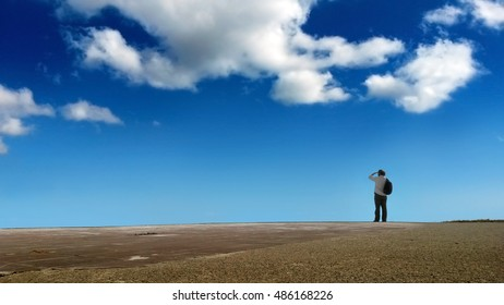 Man looking at the horizon, blue sky