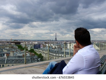 A man looking at the horizon on the foreground and the city view of Paris with cloudy sky in the background