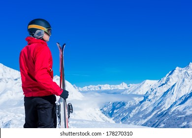 man looking at the horizon in snowy mountains