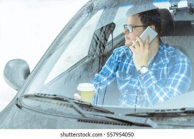 man looking info in phone and drinkig coffie while sitting in car