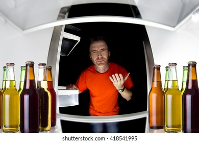 Man looking inside a fridge with bottles of beers late at night.  The man looks like a bachelor.