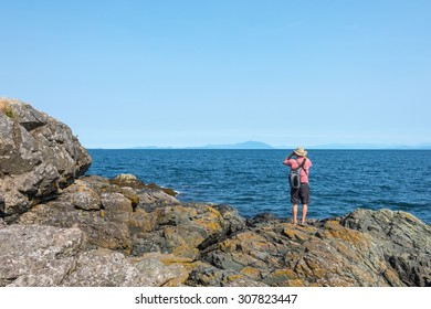 Man looking into the distance on the Pacific Ocean with binoculars off the coast of Vancouver Island, Canada