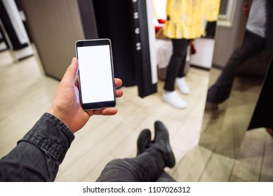 man looking into phone while his girlfriend do shopping in boutique