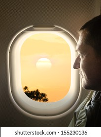 man looking into the window of the plane