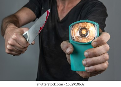 man looking with light and knife full on blood in his hand