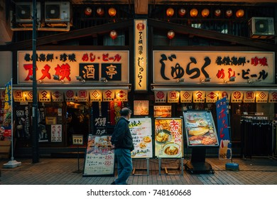 a man looking at the menu at a Japanese restaurant in Ueno, famous area for shopping / park / museum, in Tokyo, Japan, October 2017
