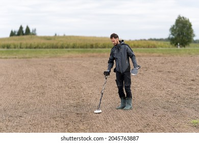 A man is looking for metal with a metal detector.