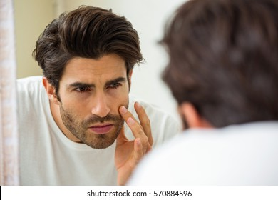 Man looking in mirror and checking his skin in bathroom
