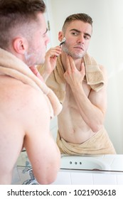 Man looking in the mirror shaving