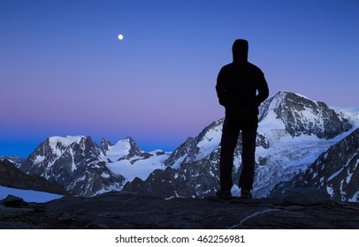 Man looking at the moon rising above the mountains in Wallis, Switzerland, during dusk.