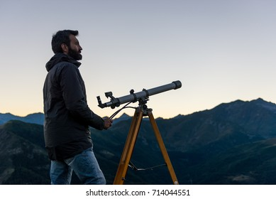 Man looking at mountain peaks near telescope in summer evening at sunset on mountain outdoor.