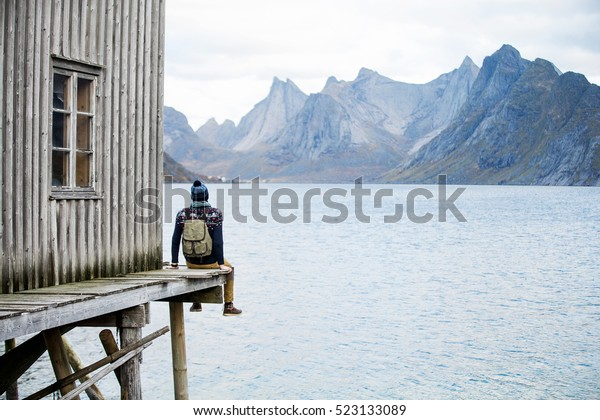 man looking at the mountains from the wooden pier
