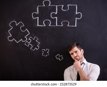 Man is looking for a new ideas for business. Blackboard with connecting jigsaw pieces.