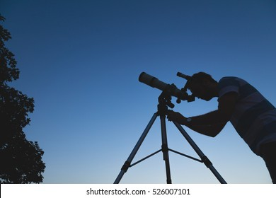 Man looking at the night sky through a telescope.