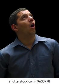 man looking up on black background surprised
