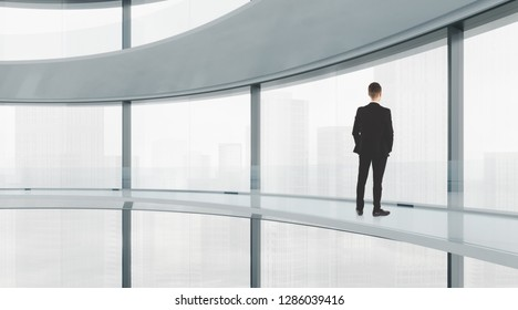 Man looking on city through the window in modern light office