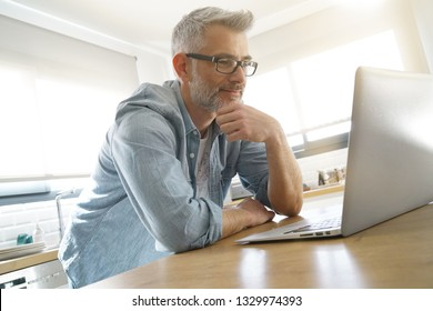 Man looking on computer at home in modern kitchen