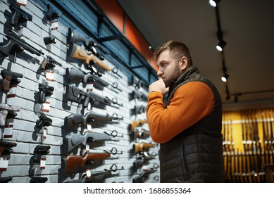 Man looking on handguns, showcase in gun shop