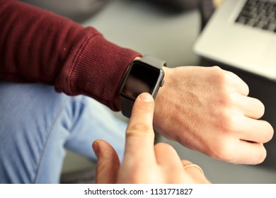 The man  is looking on his smart watches on his hand