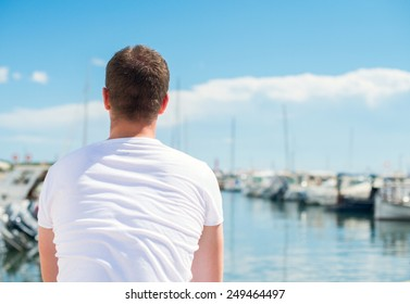 Man looking on pier with yachts.