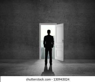man looking at opened door
