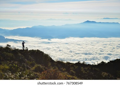 A man looking at the other hill,  Mist in mountain before sunrise in thailand of Doi Luang Chiang Dao,in chiang mai province,one of the beautiful views of Doi Luang Chiang Dao.