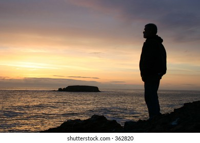 man looking out over cliff