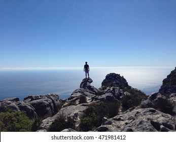 Man looking out over the horizon on a mountain with clear blue sky