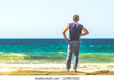 A man looking out to sea on a summer's day. He is wearing blue jeans and a sleeveless shirt.