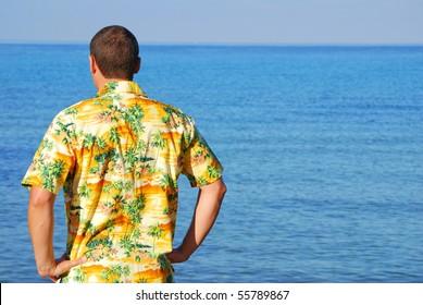 Man looking out to sea wearing hawaiian shirt