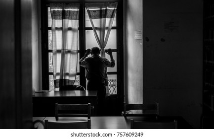 Man looking out of a window in black and white