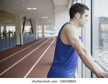 Man looking out window of indoor track