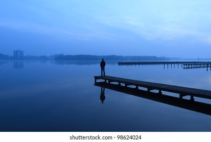 Man looking over a lake from a jetty at an early morning.