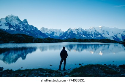 Man looking over a lake at the mountains near Chamonix, France.