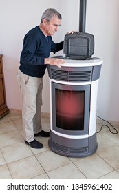 man looking in a pellet stove