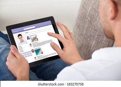 Man looking at personal profiles or comments left by viewers on a tablet computer navigating the touch screen with his finger  over the shoulder view of the screen