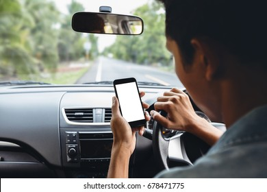 man looking at phone inside car