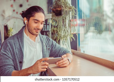 Man looking to phone, texting, sending sms. Closeup portrait of a handsome guy wearing formal white shirt, gray blouse sitting near window at a table in living room or coffee shop. Mixed race indian
