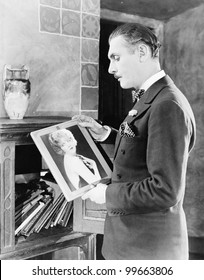 Man looking at picture of woman