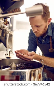 Man looking at roasted coffee beans from a roasting machine