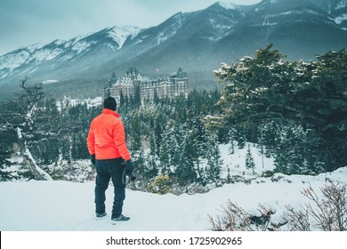 A man looking at Rockie Mountains over old building at Banff, Alberta, Canada