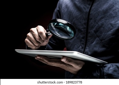 Man looking at the screen of a digital tablet with a magnifier