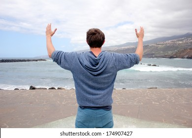 man looking at the sea with his hands raised, horizontal