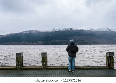 Man looking to the side from the pier on Loch Lomond near Tarbet village in Scotland. The Loch forms part of the Loch Lomond and The Trossachs National Park