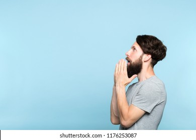man looking sideways and is amazed or impressed by smth on the left. free space for advertisement or text. portrait of a bearded guy on blue background.