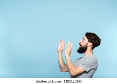 man looking sideways and is intimidated or scared by smth on the left. free space for advertisement. portrait of a bearded guy on blue background.